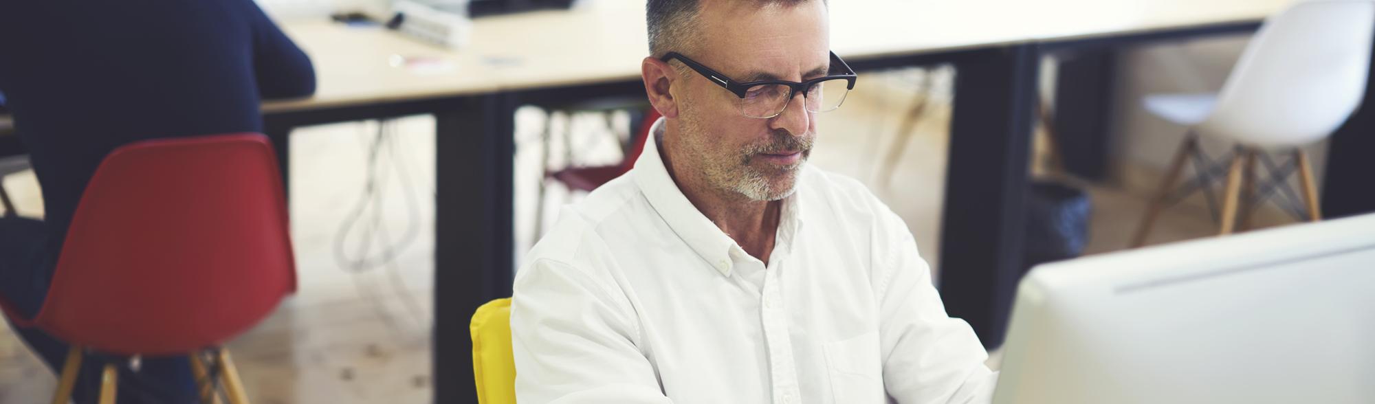 A photograph of an office worker using a computer